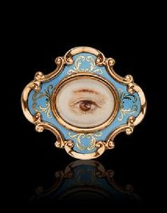 A Victorian Enamel Memorial Brooch, circa 1840. The scrolled strapwork cartouche enclosing an oval glazed compartment containing a painted miniature of a single brown eye and brow, within a powder blue enamel surround further embellished by gold foliate inlay, in 14 karat gold.