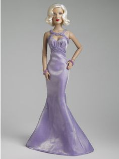 Robert Tonner Doll- Stardust/ Bette Davis™, shining star of stage and screen, commands the attention of all around her in Stardust. The glamorous starlet comes clothed in a shimmering gown with matching braided trim, gleaming beaded bracelet, pantyhose, and T-strap  high-heeled shoes.