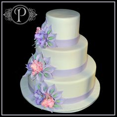 This simple yet elegant white fondant three tier round wedding cake is adorned with clusters of pink and purple gumpaste calla lilies and hand made lavender fondant orchids.