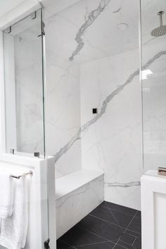 A round rain shower head is fixed to white and gray marble shower ceiling over black floor tiles ending at a marble bench fixed against a marble surround. Shower Ceiling Tile, Marble Bathroom Floor, White Marble Bathrooms, Master Bathroom Shower, Shower Floor Tile, Marble Showers, Bathroom Flooring, Ceiling Tiles, White Tiles