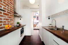 Brick wall, white gloss and wooden worktop