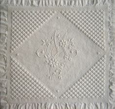 Boutis: Two fabric layers are stitched together (the top in fine white linen batiste although sometimes in red, yellow, or floral print fabric) with small, tight stitches creating the forms of traditional symbols and monograms. Then, within the lines of stitches forming a shape, one delicately inserts a tiny tuft of cotton, giving relief to the surface of the work.
