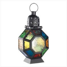 """Reminiscent of lamps of the exotic Near East, this Moroccan style candle lantern brings to mind the magic of the desert night as shadow and flame cast a haunting halo of rainbow light. Fun steam punk decor for the main stream! Loop for hanging on top. Metal and glass. 6"""" x 4 5/8"""" x 10 3/4"""" high. (Regularly $24.95) SALE!"""