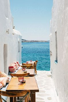 Mykonos, Greece. Picturesque alleyways with simple tables and chairs overlooking an extremely  inviting blue sea.