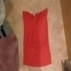Strapless dress/long shirt Orangey coral colored strapless dress ( if worn with shorts or leggings) or tube top. The bottom is a band all the way across to help fit to your body. Very soft and comfy. Great condition no stains or tears bijubi Tops