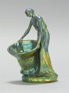 "ZSOLNAY GREEN EOSIN-GLAZED FIGURE OF A WOMAN Pecs, Hungary, Circa 1930 <br /> Depicted standing and holding a large woven basket. Gilded five churches mark. Impressed mark and 7253. Height 7.25""."