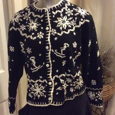 Black ski sweater with awesome details -après ski Ski sweater, perfect for a night by the fire place. This sweater is a Sz large with white skiers and snowflakes. The details on this sweater are very tricking. Never worn. Sz large. Button down front, can be worn like a cardigan Sweaters Cardigans