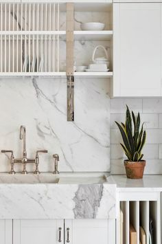 A Carrera marble farmhouse sink and backsplash bring patina to Gwenyth Paltrow's kitchen.