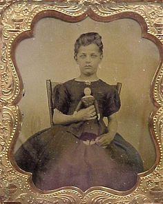 Antique photo of young girl with doll. Unusual hairstyle for the era, circa 1870 - 1890.