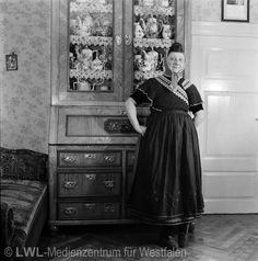 Nordrhein-Westfalen. Frau in der Volkstracht des Mindener Landes vor einem Geschirrschrank. 1950