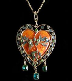 Arts and Crafts gold pendant marries a central, brightly enameled heart with a contrasting border of blue-green plique-à-jour enamel and peridot leaves and three peridot drops. Sarah Madeleine Martineau; Circa 1900