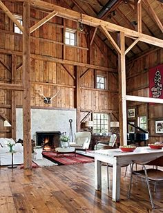 A Centuries-old Barn Gets New Life: A cozy seating area by the Fond du Lac stone fireplace features a bold striped rug and a Jens Risom chair and ottoman.