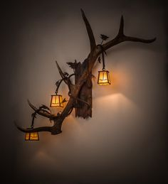 Naturally Shed Antlers are the focal point of this wall sconce design, which is adorned with three Craftsman designed Beige Iridescent art glass lanterns and a bark-like base accented with oak leaves.