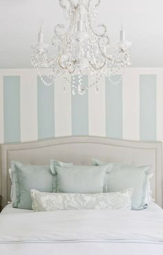 Lux Decor : Beautiful bedroom with striped blue and white vertical striped accent wall behind headboard. A natural linen colored headboard with tufting and nailhead trim is adorned with white bed linens, light blue linen euro shams and a light blue damask accent pillow. An elegant white chandelier with crystal droplets hang over the pretty bed.