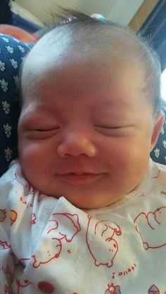 My first grandchild sleeps with smiles in heavenly peace.