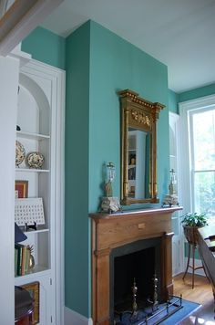 Gold mirror paired with a turquoise wall and a fireplace. Prettified parlor.