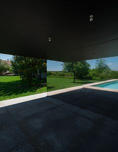 Portuguese architect João Mendes Ribeiro's swimming pool at a country houses near Chamusca da Beira. Set amongst ornamental and fruit trees, the granite-edged pool was positioned to minimise its impact on the site and existing flora. A small building at one end containing a small kitchen, wc, shower and store is clad in mirror-polished stainless steel sheets that allow the building to blend subtly with its surroundings. Photographs: do mal o menos - Text: Architecture Today