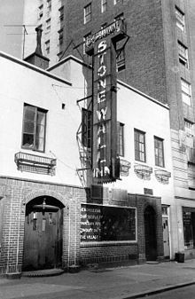 A black and white photograph of the Stonewall Inn, showing half of a sign that was placed in the window by the Mattachine Society several days following the riots