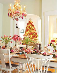 Love....Pink Christmas. A simple white-on-white interior provides a perfect backdrop for a glimmering tablescape. Tall flower arrangements in silver containers alternate with smaller bouquets to create visual interest. Country Living