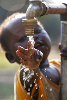 Moment: meaningful photo of a small African child touching water as it falls.: