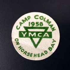 "YMCA Camp Colman 1958 patch.  Screen printed on backed felt, ~4"" diameter.  Camp Colman began in 1912, when Laurence Colman (of Seattle) took paperboys from Sunday School for a week at his property on Horsehead Bay near Gig Harbor, WA. By 1927, the Fauntleroy Y took lead for summer's programs, which included girls weeks.  In the mid 1960's, the lots around Camp were getting built up.  Camp Colman moved to its current location on Key Peninsula in 1968, where hundreds of campers come every…"