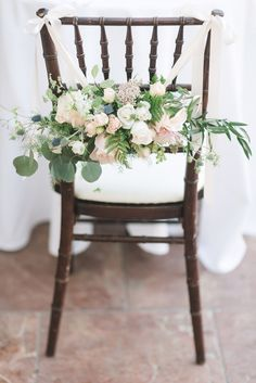 Floral chair backs for the bride and groom. Photo by Ryanne Bee