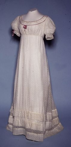 c. 1817 Evening dress, white muslin and tambour work embroidery, trimmed with purple silk ribbon. The bodice is shaped by gathering at the neck edge and under the bust with drawstrings, which tie at the back and fasten with hooks. Hooks of flattened copper or brass wire were used from about 1815. Bowes Musuem, 1984.16.2/CST.2.735.