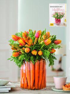Für diese österliche Blumendeko benötigt ihr:- je 10 orange-gelbe und orange-grüne Tulpen- 2 Bund Karotten mit Grün- 1 zylindrische Vase mit großer ÖffnungSo geht's: Karotten gründlich putzen. Platziert die Karotten mit dem Grün nach oben am Rand der Vase. Die Karotten sollen so dicht