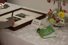 Guest book, picture frame signing, and a glimpse of one of the wonderful flower arrangements by Martha Swineford. Photo by Brienna McWade.