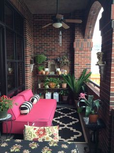 Small, private brick balcony with fan and lots of plants