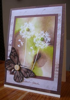 the dandelion is stamped twice onto the alcohol inked background and white embossed. The butterfly is cut out from patterned paper and  buttons are used to accentuate the flowers and a vintage button for the butterfly.
