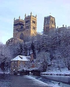 A winter view showing Durham Cathedral with three large towers looming high on a craggy cliff above a river bordered with snow-covered trees...