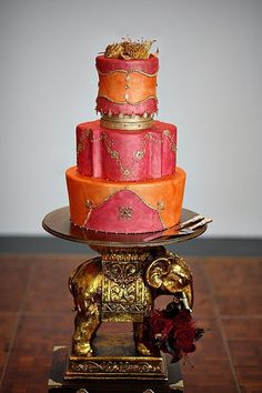 Pink and orange Indian wedding cake on a gold elephant stand