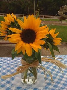 Reception center pieces: Sunflowers in mason jars with blue checkered table cloth