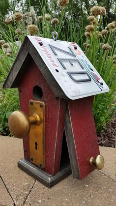 """The Bungalow Made of rough pine with an old license plate as the roof along with antique hardware. It has a side door for removing old nest material. Birdhouse hole is 1 ¼ inches in diameter. Approximate dimensions: 12"""" inches tall 8"""" inches wide 6"""" inches deep Currently there are 3 Red available. PLEASE SPECIFY WHICH RED ONE YOU WOULD LIKE! EXAMPLE LICENSE PLATE ENDING IN ZED / 43 or 388 Thank you! Tim"""