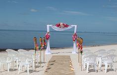 Beautiful tropical beach wedding setup, colorful decor, with runner, shells, tiki torches, such and islandy flair! www.ezweddingsinparadise.com