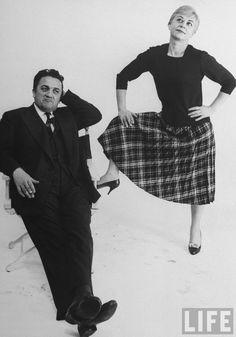 Italian dir. Federico Fellini (sitting in director's chair) and actress wife Giulietta Masina (w. leg propped on chair) posing in studio . New York . 1959 . Photo by Gjon Mili