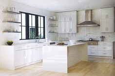 Modern kitchen features white lacquered cabinets paired with white quartz countertops and an oversized white marble subway tiled backsplash.