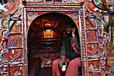 A passenger talks on his phone while travelling in a decorated minivan in Rawalpindi.