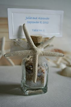 X 9 Wedding Favors - Place Card or Table Number Holder - Beach in a Bottle - Starfish Sea Shells - Sand. $33.75, via Etsy.