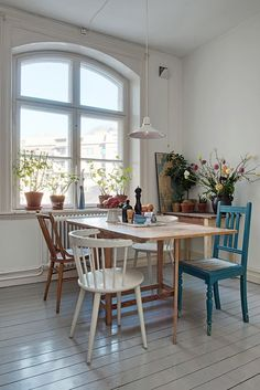 Dining room inspiration. Wooden table. Mismatched chairs. Lots of plants and flowers. Art. White.