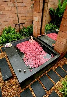 I'll have what she is having... rose petals in a luxurious outdoor spa with black paving stones and surround and brown river rock.