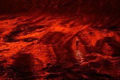A member of the expedition walks on the caldera's cooled lava floor, turned red by the reflected glow of Nyiragongo volcano's lava lake.