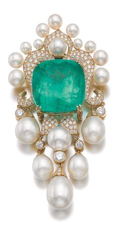 EMERALD, CULTURED PEARL AND DIAMOND PENDANT/BROOCH, AMR SHAKER Set with a cushion-shaped emerald weighing 104.97 carats, to a decorative mount highlighted with brilliant-cut diamonds and cultured pearls, suspending a similarly set fringe, signed Shaker.