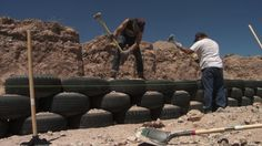 Earthship Wall Being Built:  Tires are set like bricks and rammed full of dirt