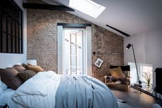 The bedroom in this newly renovated building has the original beams and an exposed brick wall, which is mixed up by a glass window to the hallway and white walls. I like the brown and black look of the walls … Continue reading →