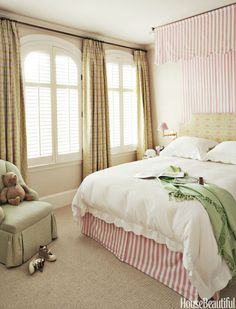 """The daughter's room is very feminine,"" says Weiss, who used Pindler's Mayer stripe for the canopy and bed skirt, and Raoul Textiles' Amijao for the headboard and curtains."