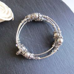 Silver grey pearl memory wire bracelet This gorgeous bracelet is made with 10mm gleaming light grey Swarovski Elements crystal pearls, complemented by super sparkly grey faceted crystals. The beads are separated with silver plated tube beads and antique silver plated accent