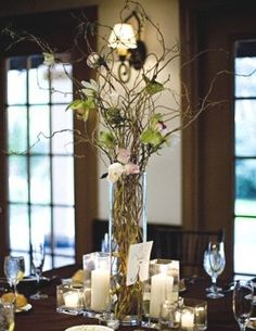 i like this idea, not the flowers in it, would want others, but really like this centerpiece idea with a taller stick arrangement in middle, with the candles around it like this, maybe add a mid sized floating candle with a flower in it