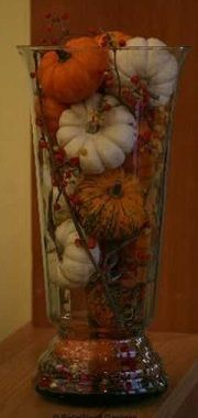 Create quick, inexpensive centerpieces for a fall wedding by filling a tall vase with pumpkins.